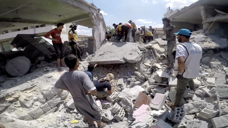 Witte Helmen doorzoeken de restanten van een gebouw in Idlib na een bombardement door het regeringsleger.  Beeld Reuters