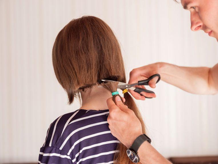 Oekraïense Alina laat haar mooie lange haar afknippen. De man betaalde haar er omgerekend 57 euro voor. Beeld Tom Skipp