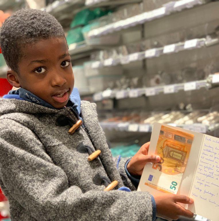 Sébastien met het kerstkaartje en het briefje van vijftig euro dat hij kreeg van de 'Secret Santa'.