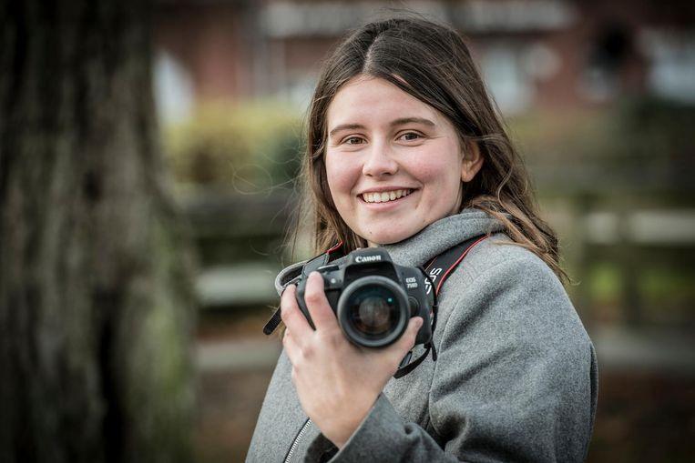 Flore Verbeke moet haar fototoestel bedienen met één hand, omdat ze haar rechterarm niet kan gebruiken.