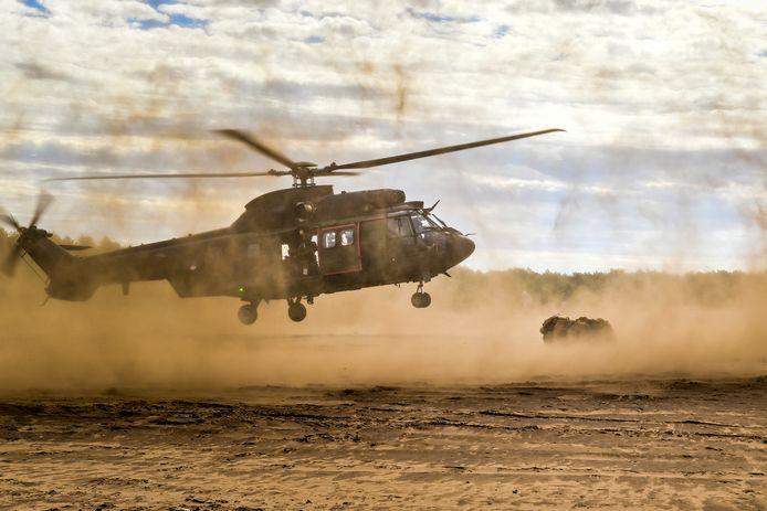 Een Cougar transporthelikopter gaat acht leden (r.)van de Luchtmobiele Brigade ophalen die samengepakt meteen ook grondbaken zijn. Helikopters van vliegbasis Gilze-Rijen oefenden donderdag op de Oirschotse Heide zandlandingen, die met veel stof gepaard gaat.