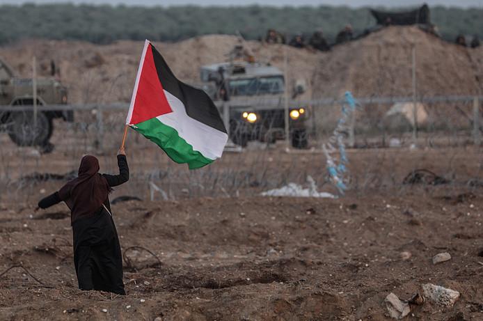 Een Palestijnse vrouw zwaait met een vlag naar Israëlische soldaten.