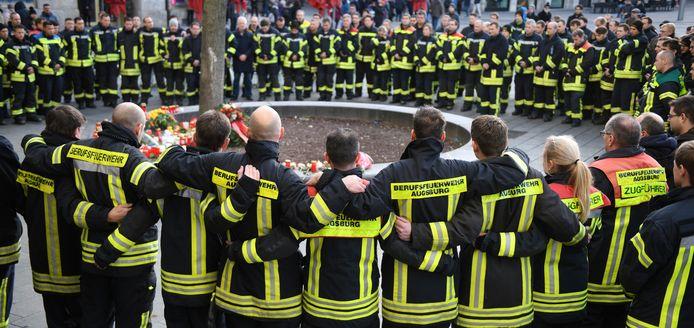 Brandweerlieden uit Augsburg kwamen vanmiddag bijeen op het plein waar hun collega vrijdagavond na een treffen met een groepje jongeren zo ernstig gewond raakte dat hij onderweg naar het ziekenhuis aan zijn verwondingen bezweek.