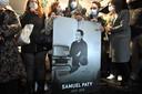 Vrienden en familie houden een foto vast om Samuel Paty te eren tijdens een witte mars in Conflans-Sainte-Honorine, nabij Parijs.