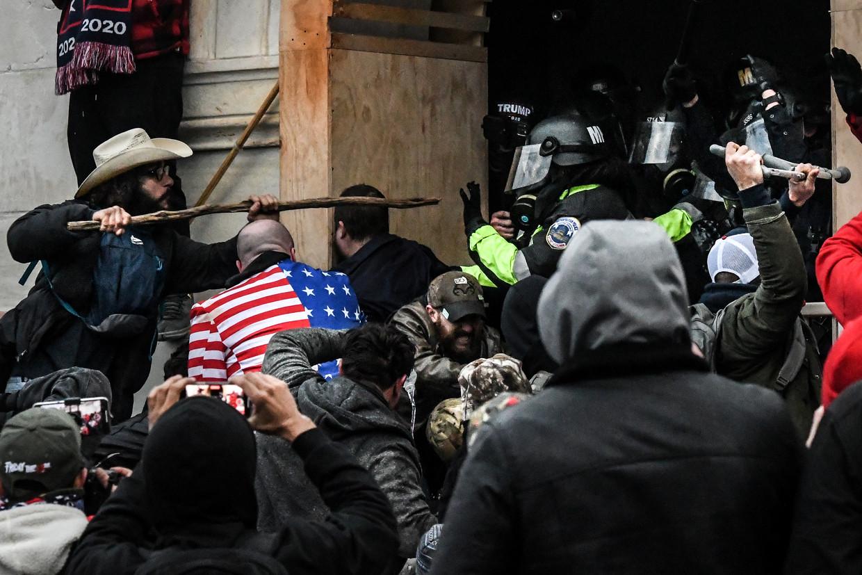 Aanhangers van Donald Trump vechten op 6 januari met de politie, die hen buiten het Capitool probeert te houden.   Beeld Stephanie Keith / Reuters