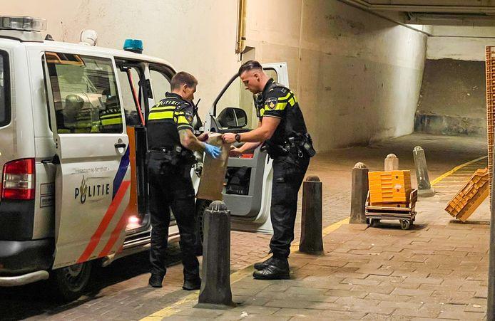 Agenten stoppen het aangetroffen alarmwapen in een bruine zak.