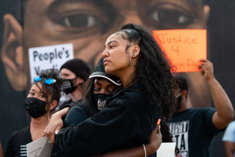Twee vrouwen omhelzen elkaar voor een muurschildering van George Floyd op 20 april 2021 in Atlanta, Georgia, na de veroordeling van de politieman die in mei vorig jaar George Floyd dooddrukte. Beeld AFP