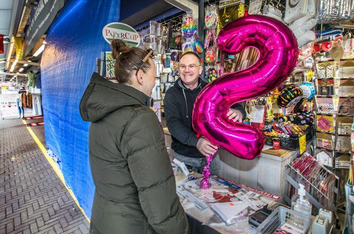 Marktkoopman in feestartikelen Eric Alsem op de Haagse Markt heeft door corona zijn hele kraam moeten afsluiten met zeilen.