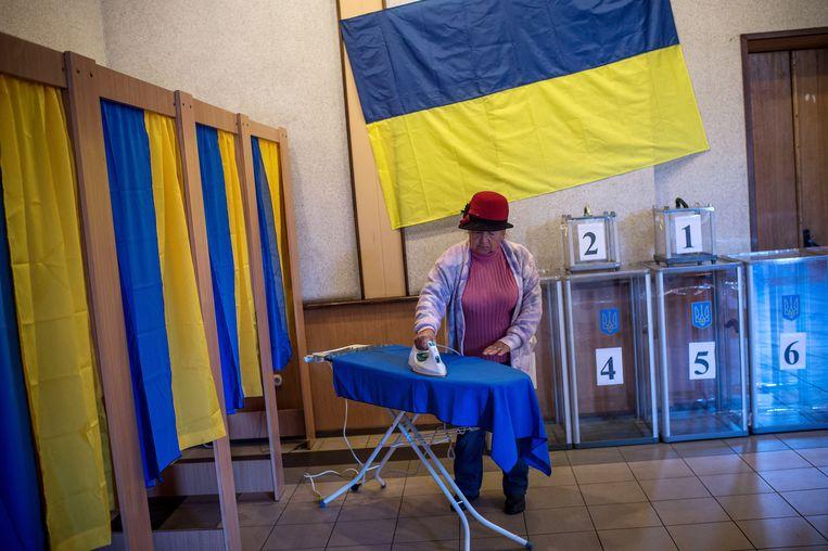 Een medewerker van een stemlokaal in Oekraïne strijkt het gordijn van een stemhokje Beeld getty