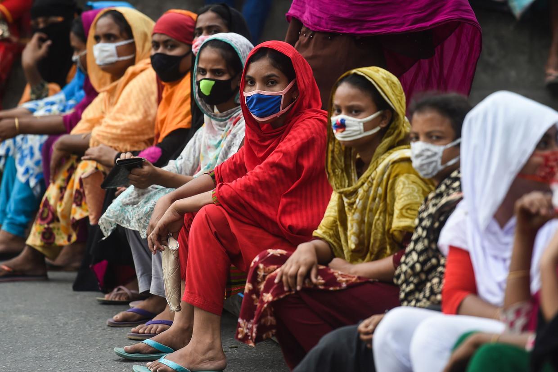 Fabrieksarbeiders in Bangladesh blokkeren de weg in een poging achterstallig salaris op te eisen. Door de crisis zien zij de hele kledingindustrie in gevaar komen. Beeld AFP