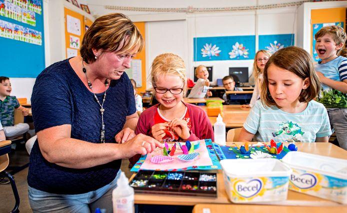 Juf Xandra Baert en groep 3 van de Fatimaschool knutselen moederdag- cadeautjes.