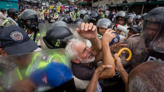 Deze man kon zich maar moeilijk bedwingen tijdens het protest en wordt stevig vastgepakt door de ordediensten.