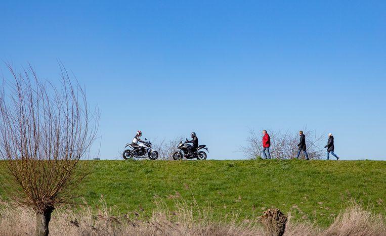 Dagjesmensen op de dijk langs rivier de IJssel tussen Veessen en Zwolle. Beeld Hollandse Hoogte / Rob Voss