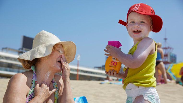 Een oma en haar kleinkind smeren zich in met zonnebrandcreme op een zomerse stranddag in Scheveningen. Beeld anp