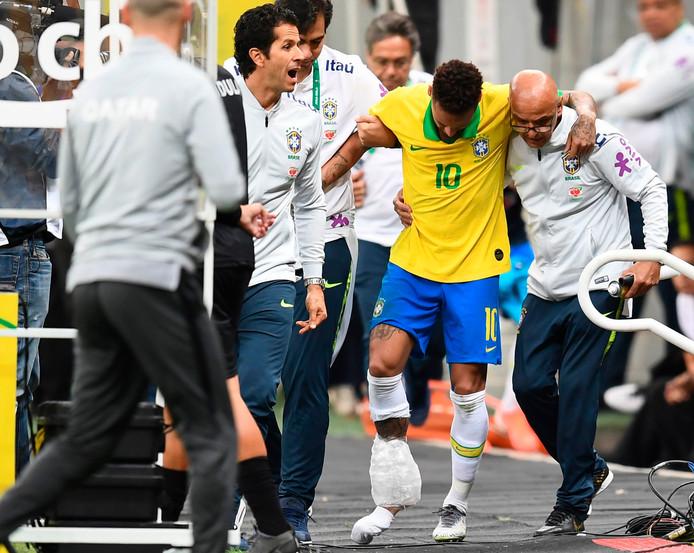 Neymar verlaat het veld met ijs om zijn enkel.