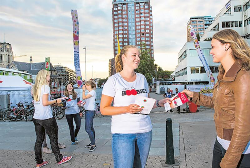 Anniek Velthuizen en haar hardloopcollega's aan het flyeren voor hun actie Save the boobies.