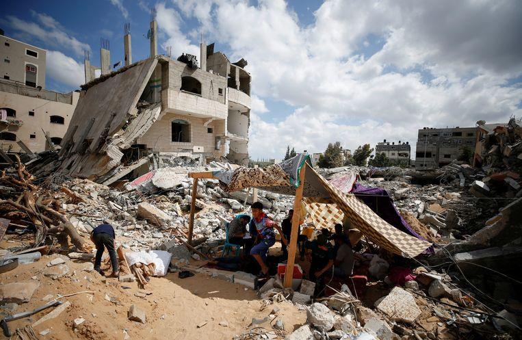 Een familie in Gaza verblijft tijdelijk in een tent op de plek waar hun huis stond. Beeld Reuters