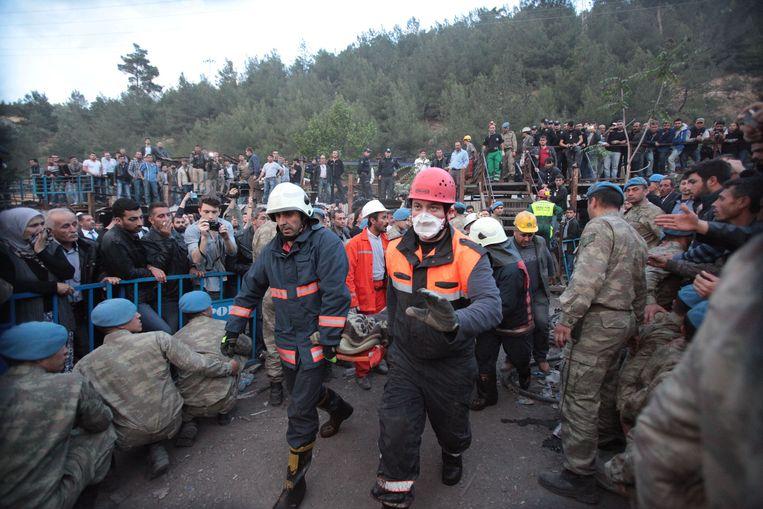 Reddingswerkers dragen een lichaam weg, terwijl de spanning aan de mijn te snijden is. Beeld GETTY