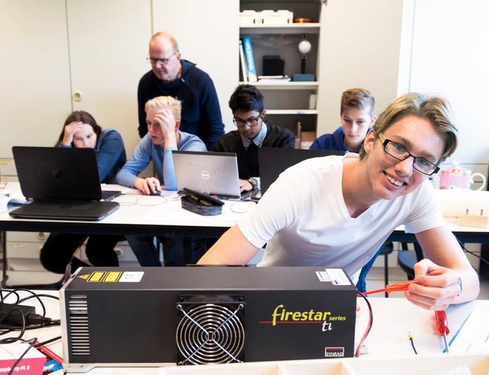 Leerling Tim, van het Veenlanden College, sleutelt aan de laser. Op de achtergrond maakt docent Bart Kappé met leerlingen software voor robots