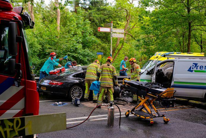 Brandweermannen proberen de automobilist uit zijn benarde positie te bevrijden.