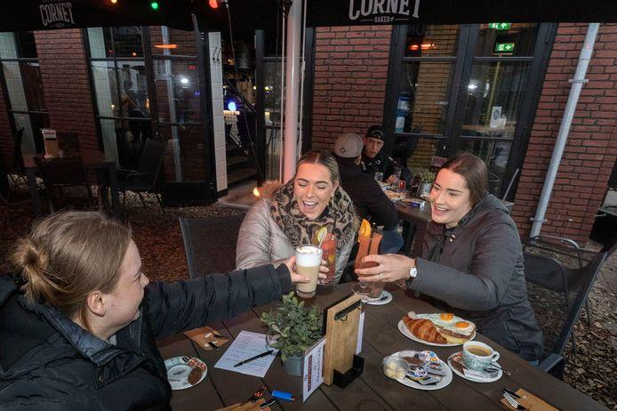 """Iris van den Biggelaar, Romy Hoogers en Romy Smits (vlnr) zijn vanochtend om 6 uur neergestreken op het terras van De Vijfhoeck in Helmond en vieren dat met een cocktail. Op de achtergrond Maarten van Kraay en Ryan Lenssen uti Helmond die strak om 6 uur aan het bier zijn gegaan. ,,Daar is het nooit te vroeg voor."""""""