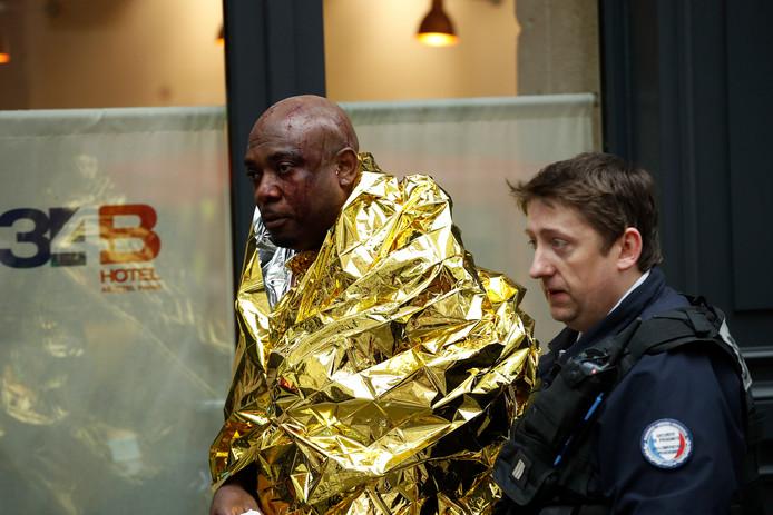 Een agent helpt een gewonde man die in een hotel in de straat verbleef.