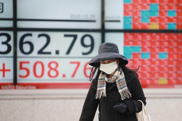 Een vrouw loopt dinsdag 29 december 2020 langs een elektronische aandelenraad van een effectenbedrijf in Tokio. De aandelen stegen dinsdag in Azië na het sluiten op recordhoogtes op Wall Street. De Nikkei 225-index in Japan doorbrak een hoogste punt in bijna 30 jaar nadat president Donald Trump maandag een economisch hulppakket van $ 900 miljard had ondertekend, wat bijdroeg aan de onzekerheid toen regeringen opnieuw pandemiebestrijdende reizen en zakelijke beperkingen opleggen die de wereldwijde economische activiteit dreigen te drukken Beeld AP