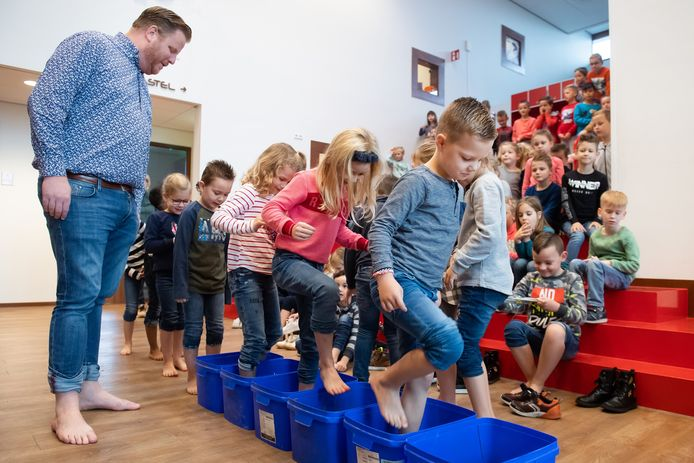 De kinderen van de Talente basisschool mogen, nadat wethouder Thomas Melisse het voorbeeld heeft gegeven, het blotevoetenpad lopen. Het maakt deel uit van het 50-dingen boekje van stichting Groen Ontmoet.