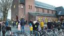 Ouders en kinderen verzamelen zich bij het kerkgebouw voor de eerste schooldag.