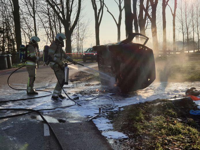 De brandweer moest de auto op zijn kant trekken om het vuur goed te kunnen blussen.
