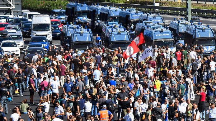 Politiebusjes blokkeren de snelweg die demonstranten proberen te bezetten.