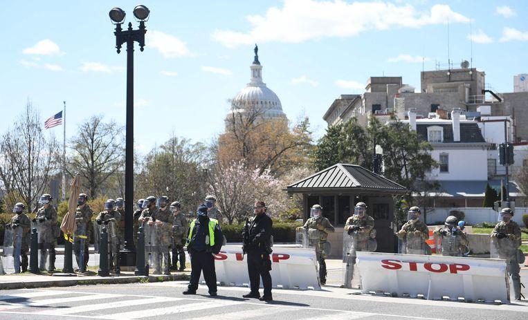 Politie en militairen sluiten de weg af in Washington DC, op de achtergrond het Capitool. Beeld AFP