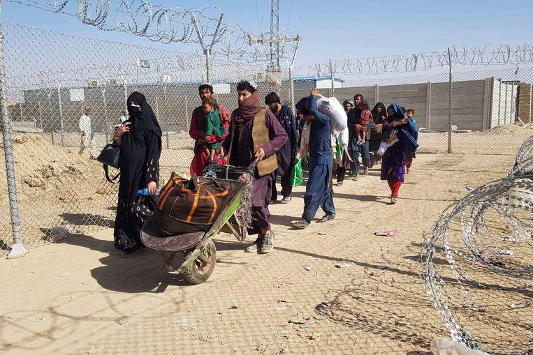 Afghanen steken de grens met Pakistan over in Chaman. Beeld AFP