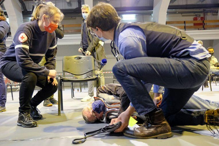 Een proefpersoon veinst een flauwte en wordt meteen bijgestaan door medisch personeel, dat de man wegvoerde op een draagberrie. Beeld Marc Baert