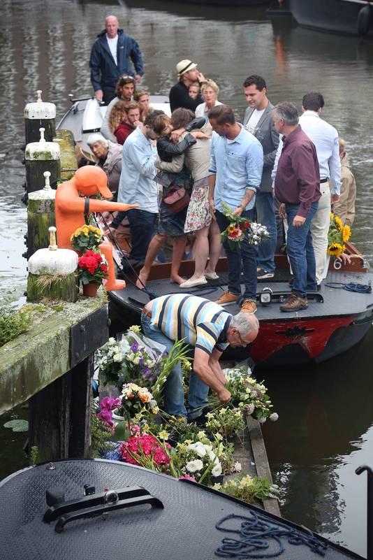 Vrienden en familieleden herdenken Rein en Desiree bij het Leemmannetje, dat sinds de vliegramp een rouwband draagt.
