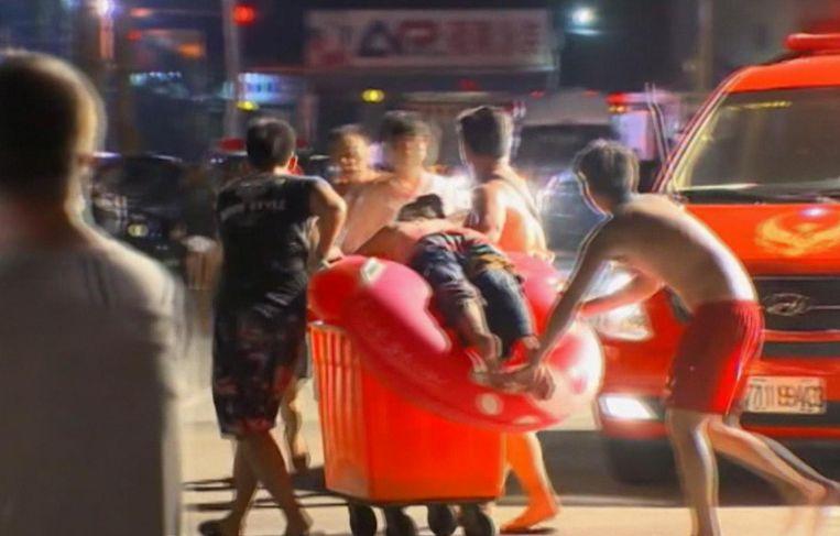 Een gewonde toeschouwer wordt afgevoerd.