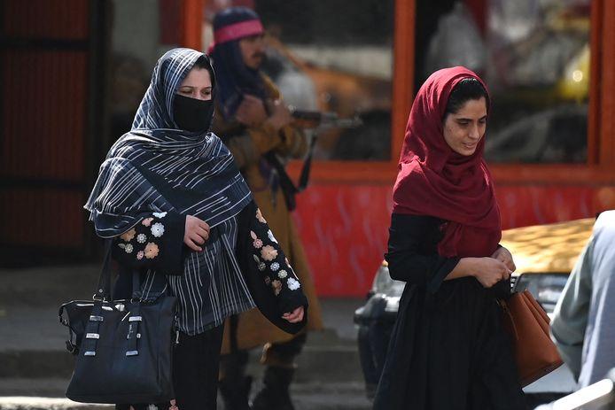 Twee vrouwen wandelen voorbij een talibanstrijder in Kaboel.