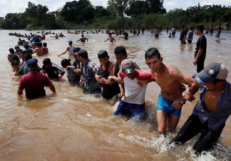Migranten maken een ketting door de rivier die de grens is tussen Guatemala en Mexico. Beeld Reuters