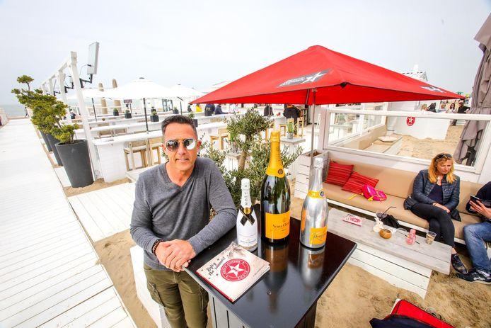 Zaakvoerder Glenn Van Hoeck bij enkele flessen champagne die je in 'Beach Number 1' kan kopen.