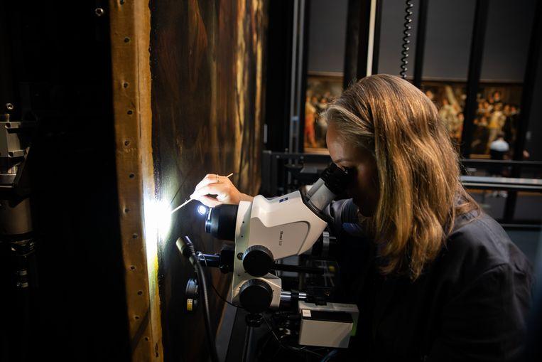 Restaurator Susan Smelt neemt vernis af van de Nachtwacht.  Beeld Rijksmuseum