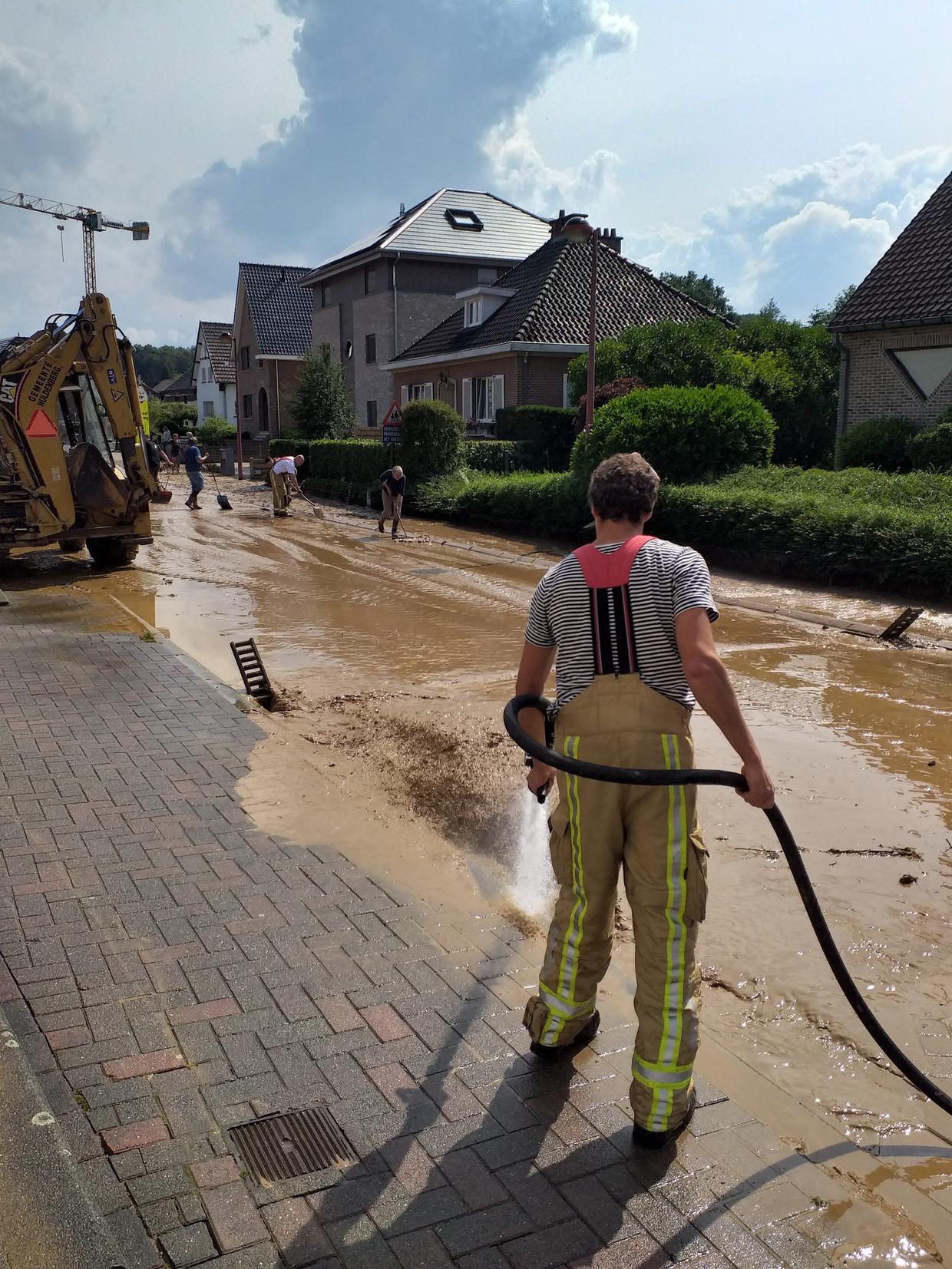 Modder ruimen in de straten van Huldenberg.