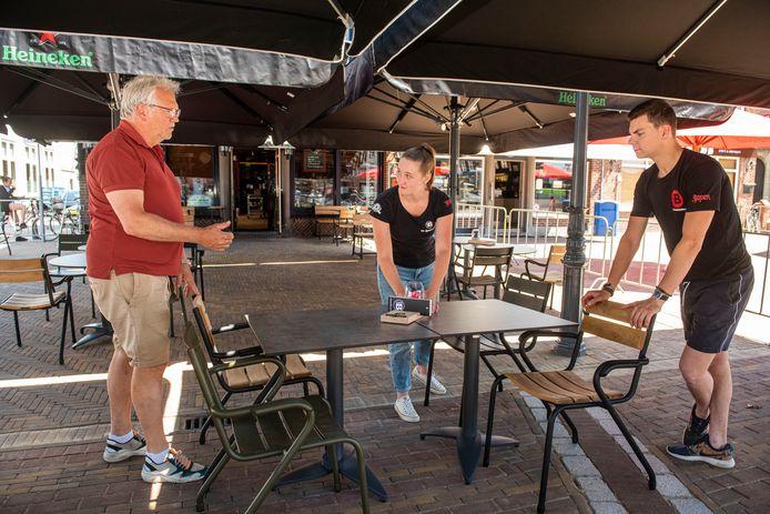 Horeca-ondernemers zijn bezig met de proefopstelling van  terrassen. Peter van de Wiel (links,) eigenaar van café De Bakkerij in Zevenbergen, kijkt vrijdag met zijn personeel hoe de  tafels en stoelen - met de anderhalvemetermaatregel van het RIVM - het beste kunnen staan.