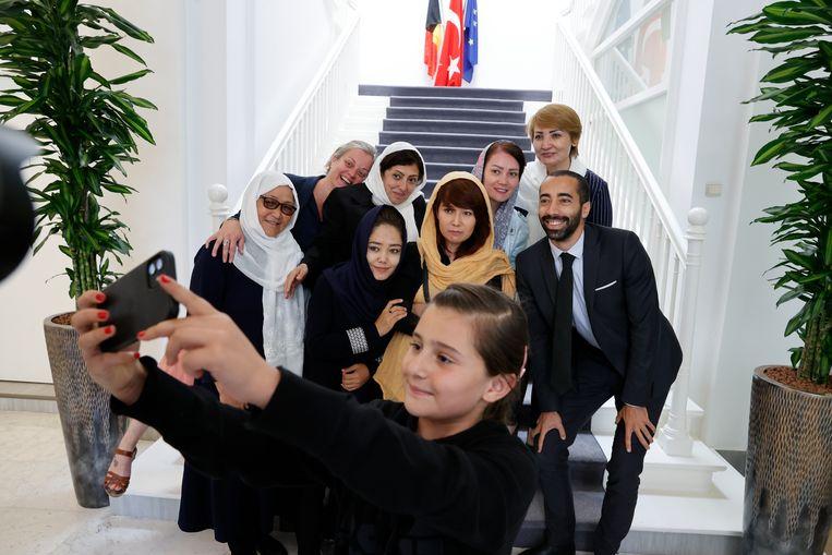 De dochter van Shahnaz Saha (links in beeld) neemt een selfie met de staatssecretaris. Beeld Jan De Meuleneir / Photo News