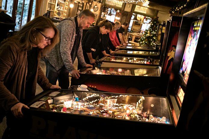 Geconcentreerde deelnemers van het eerste Heezer Open Flipperkasttoernooi hebben alleen oog voor de speelballen in hun flikkerende en pingelende machines.