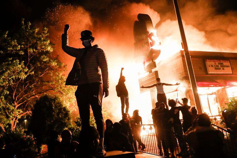 Vier dagen na de dood van George Floyd staat Minneapolis in brand. Een fastfoodrestaurant vlak bij een politiekantoor gaat in vlammen op. (John Minchillo) Beeld AP