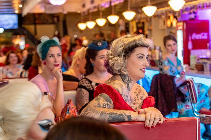 Mede-deelnemers van voorronde miss Pinup in Tom's Diner in Roosendaal, kijken vol verwondering naar de presentatie van één van hun concurrenten, die zich presenteert met een liedje over zichzelf met zang en op de ukelele.