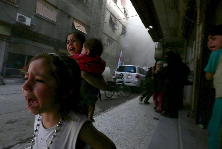 Kinderen rennen verschrikt weg na een bominslag in de Doumawijk van Damascus. Beeld Bassam Khabieh / REUTERS