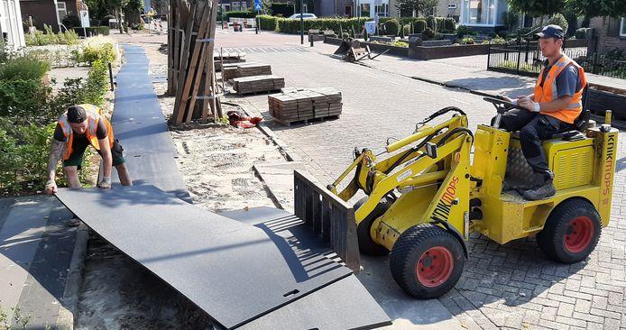 Smalle matten vervangen de opgeruimde stoeptegels, bij de start van de reconstructie van de 'Traverse' door Heeswijk-Dinther.