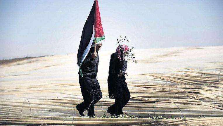 Een man en vrouw demonstreren in de Gazastrook met een Palestijnse vlag en een olijftak tegen Israëlisch beleid. Beeld afp