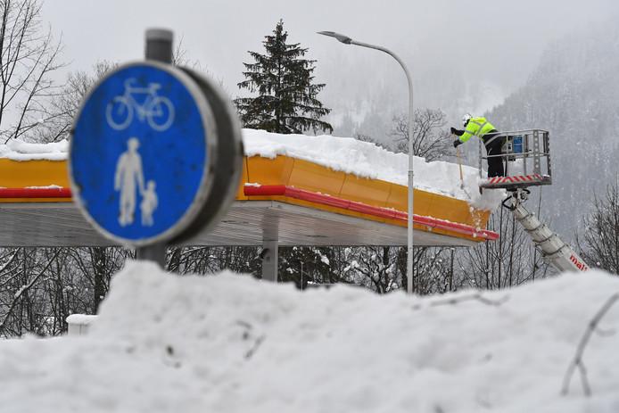 Een man verwijderd sneeuw van de overkapping van een pompstation.